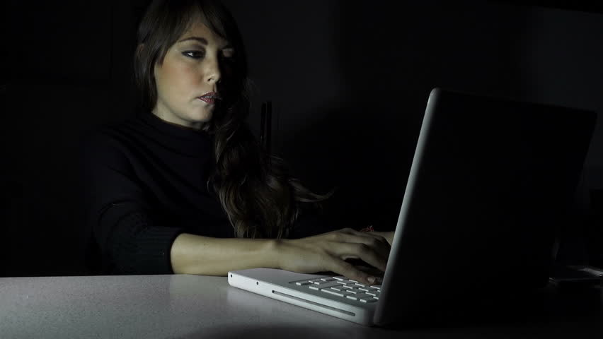 Young woman using a laptop computer in the darkness  | Shutterstock HD Video #11044640