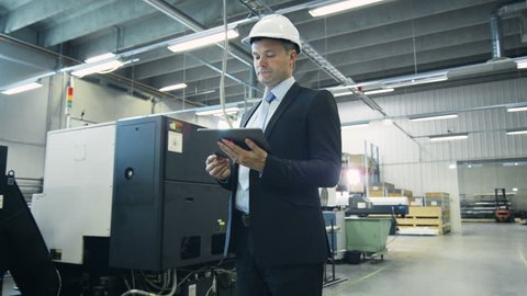 Businessman is Using Tablet PC in Industrial Environment. Shot on RED Cinema Camera in 4K (UHD).