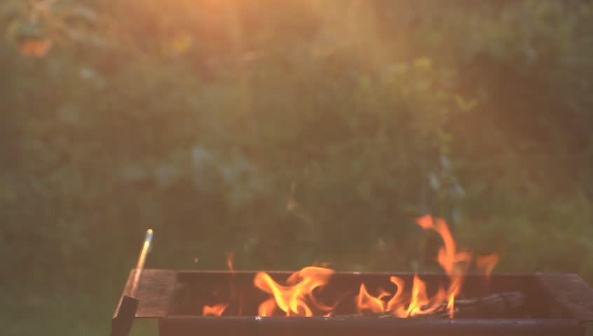 Preparing the grill for the barbecue. Coal burns in a brazier. Sunset light.