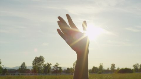 SLOW MOTION CLOSE UP: Sun shining through fingers of a waving hand