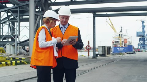 Business People in Safety Vests Using Tablet in Industrial Environment. Shot on RED Cinema Camera in 4K (UHD).