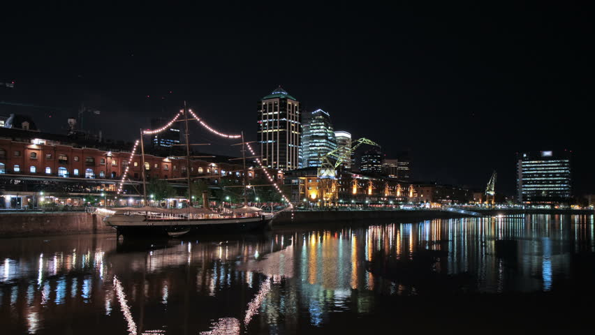 Puerto Madero harbor, Buenos Aires, at night, showing restaurants, a boardwalk, a museum ship and downtown skyscrapers.Wide angle photo time-lapse (Argentina; Mar 2011; DSLR).