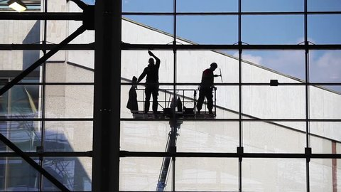 Two unrecognized washers washing windows.Industrial Climbers, facade cleaning