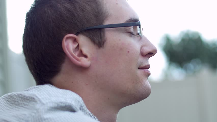 Man with glasses takes deep breath in