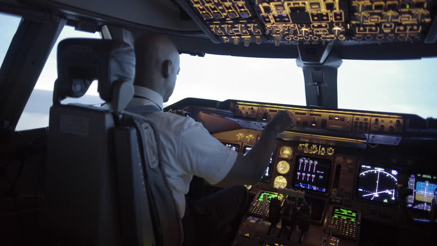 Dramatic angle from rear of 747 cockpit as African American pilot makes a long turn over an area of northern California, USA. Stabilized hand-held camera, mid shot, originally recorded in 4K at 30ps