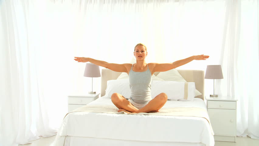 Pretty blond woman doing exercise of relaxation on her bed