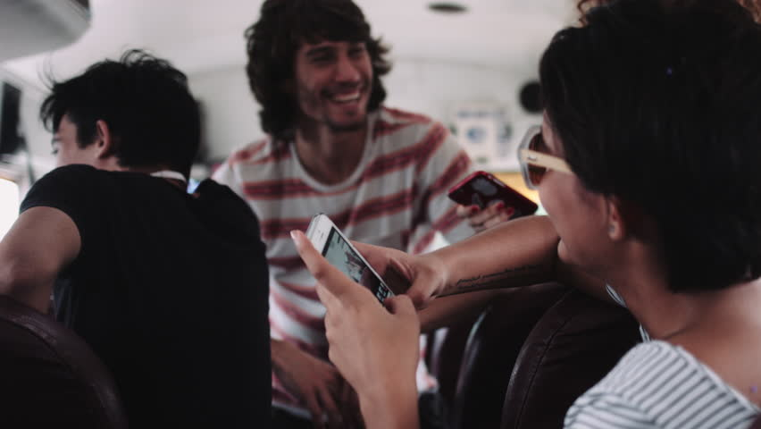 Male and female friends sitting and talking in bus, using mobile phone