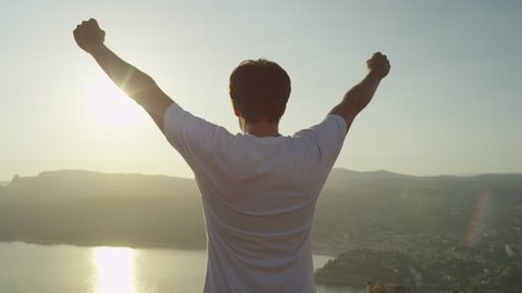 SLOW MOTION CLOSE UP: Cheerful young man raising his hands high on top of the big mountain above the ocean at beautiful golden sunset
