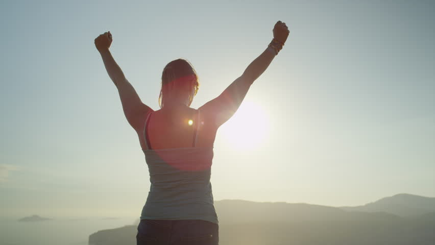 SLOW MOTION CLOSE UP: Young woman raising her hands on top of the mountain #11223080