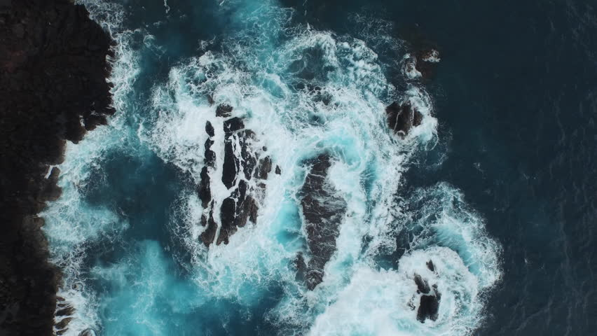 Aerial of the ocean waves washing up on a black basalt rock in Hawaii.