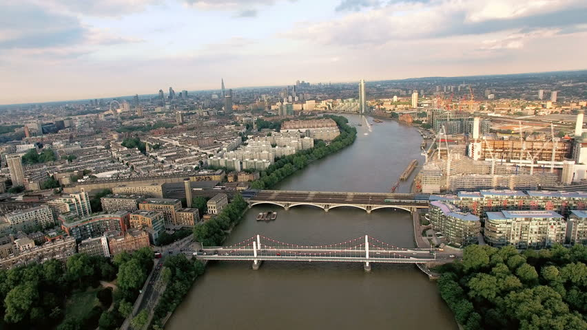 4K Aerial View Above The Thames River and Bridges in London. Cars Passing on a Bridge and a Train on a Railway Bridge on a Sunny Day.
