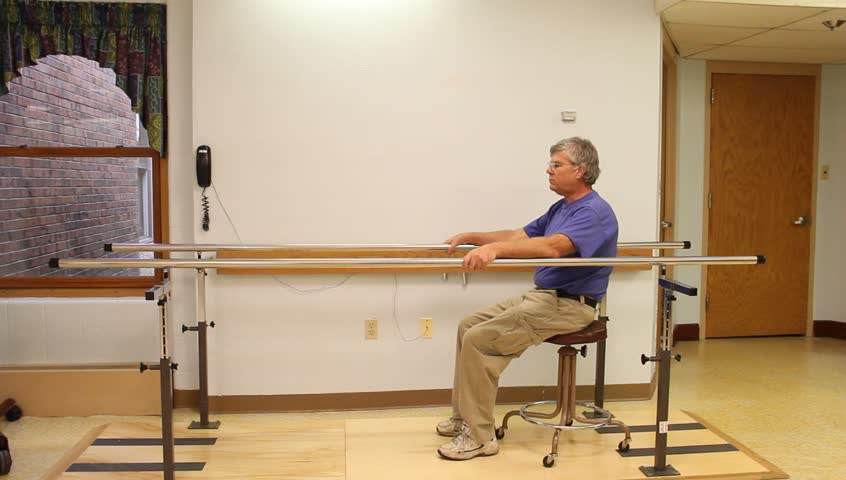 Patient walking on parallel bar for physical therapy