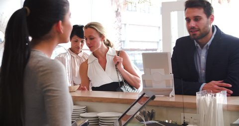 Customers ordering and paying at the counter in a cafe