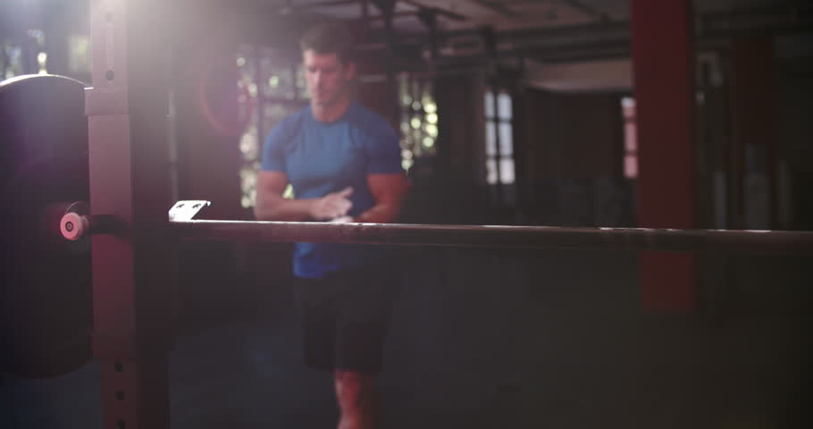 Man chalking hands before lifting barbells in a gym | Shutterstock HD Video #11319470