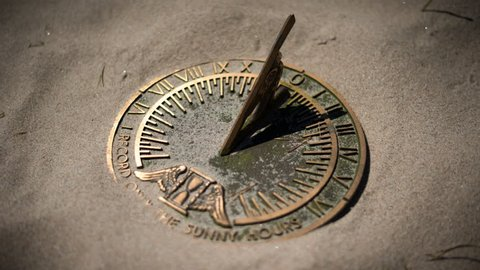 Time lapse of a brass sundial in the blowing sand with moving shadows on a sunny afternoon.
