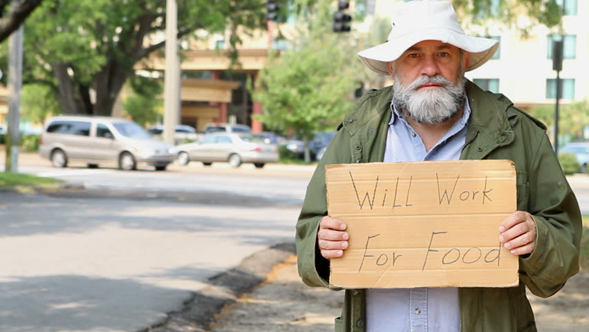 "Homeless man stands at the side of the road holding a sign that says ""Will Work For Food"""