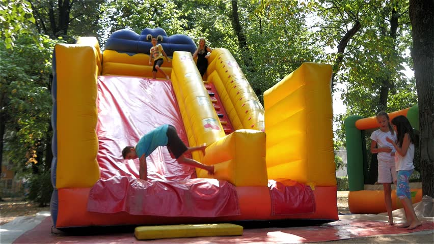 Group Of Children Climbing Go Down The Big Rubber Slide On Playground In Park
