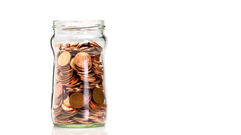 Glass bottle slowly filling with copper coins, isolated on a white background, saving money concept