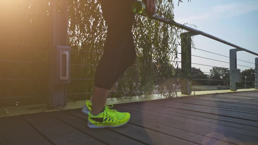 Runner woman feet in the city exercising outdoors. Slow Motion, Steadicam stabilized shot. Sportswoman wearing barefoot sports shoes while training on the sunny city bridge. Slow motion. Lens Flare.