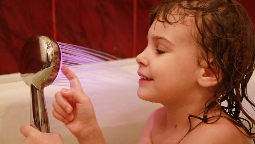 young girl play in the bathroom with led light spray