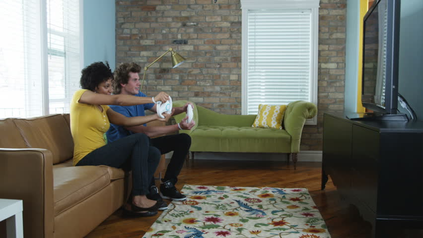 Young couple playing Nintendo wii in the living room | Shutterstock HD Video #11527490