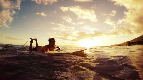 Young Man Paddles by the Camera on a Longboard Through the Sunset. Warm Tone. Slow Motion. Sun Flare Instagram Filter. POV Point of View