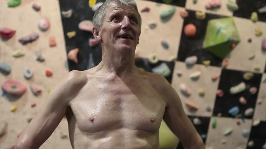 Happy and breathing heavily mature climber, standing in climbing gym #11535890