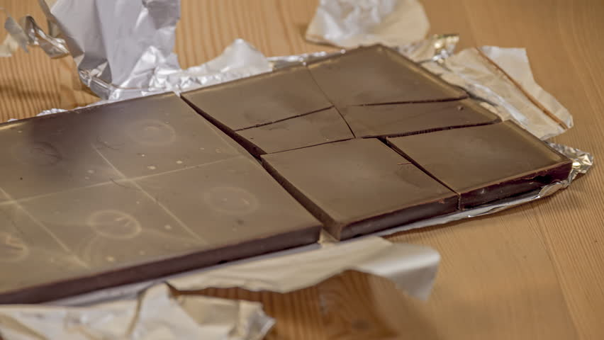 Process of unwrapping a dark chocolate bar, breaking in into serving pieces, eating it (off camera), and discard the foil wrapper, stop motion