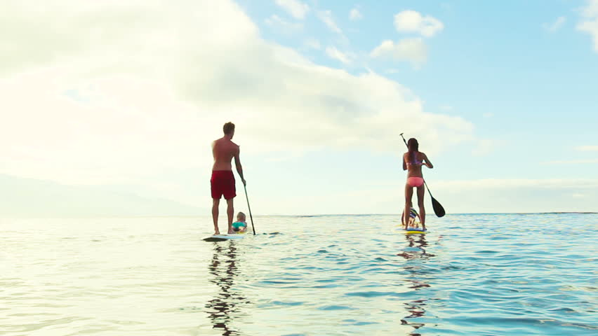 Stand Up Paddling in at Sunrise. Family of Four. Summer Fun Family Vacation Healthy Lifestyle. Tandem SUP.