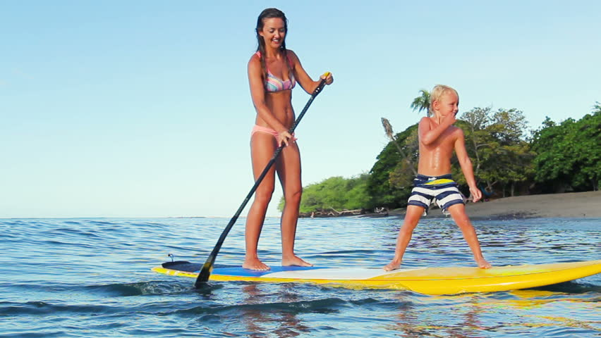 Cute Young Blonde haired Boy Falls Off Stand Up Paddle Board with a big Splash. Summer Fun Family Vacation Healthy Lifestyle. Tandem SUP.