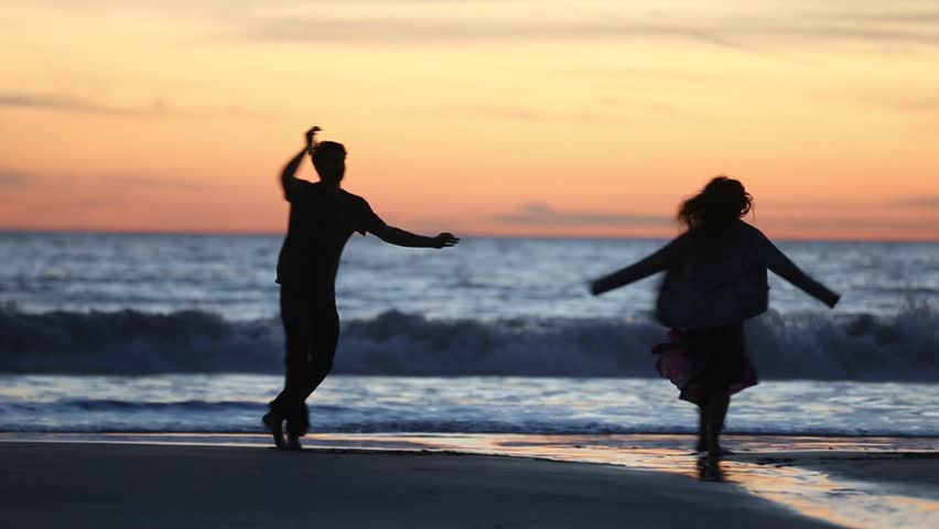 Carefree dancers by the beach during golden magic hour moment. Real life and candid shot of people dancing spontaneously by the beach during sunset. Man and woman spinning freely, happily, and at ease
