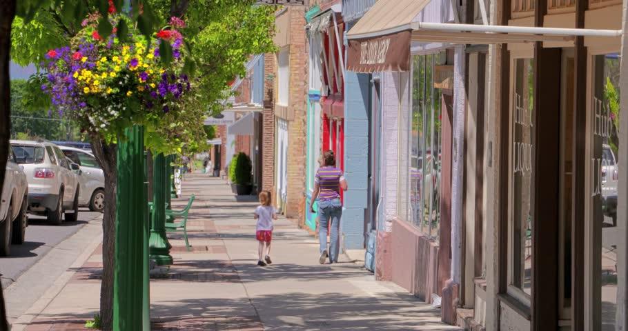 People walk down a beautiful small town sidewalk.