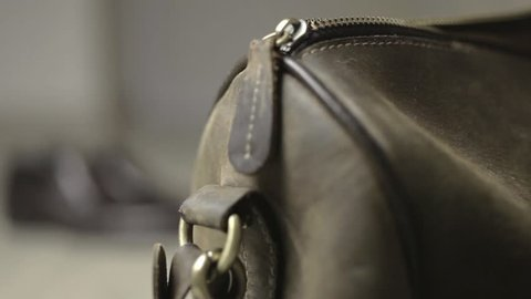 A man is zipping and unzipping his travel bag - very close shot