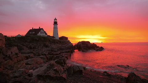Establishing aerial shot of a gorgeous sunrise in Maine capturing a Lighthouse. Vivid colors of purples, pinks and yellows are reflected in the water.
