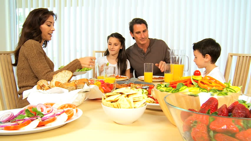 Young Family At Table Together Eating A Healthy Meal Stock Footage Video 1166770
