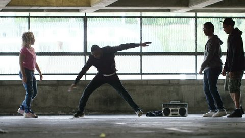 4K Male breakdancer performs in front of a group of friends as they cheer him on, in slow motion