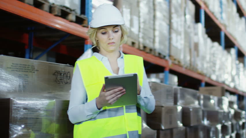An Attractive Female Warehouse Employee Wearing High Visibility Clothing And A Hard Hat Is