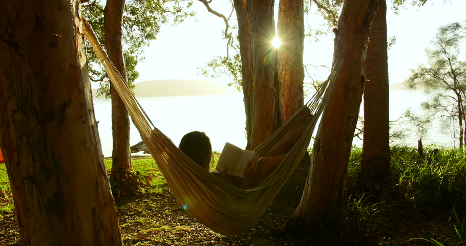 Woman Relaxes Reading Book In Hammock Swaying Gently In