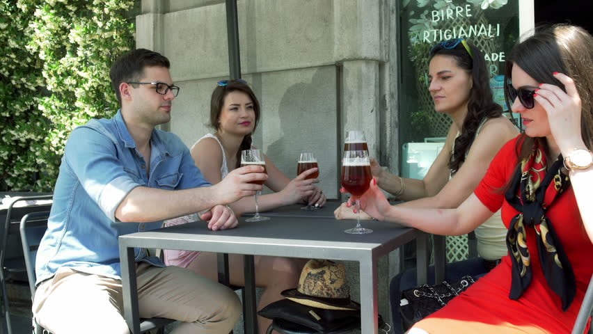 Happy friends cheers beer in the cafe and smiling to the camera  | Shutterstock HD Video #11723660