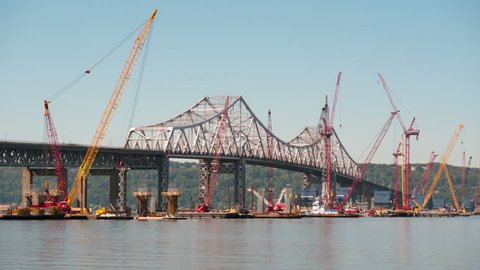(Time-lapse/Zoom-in) Barge mounted cranes work on construction of the new Tappan Zee Bridge as traffic crosses the existing Tappan Zee Bridge on September 15, 2015 in Tarrytown.