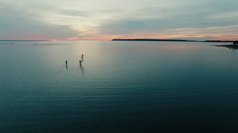 Aerial drone shot of windsurfer and paddleboarder at sunset. Shot in 4K (UHD).