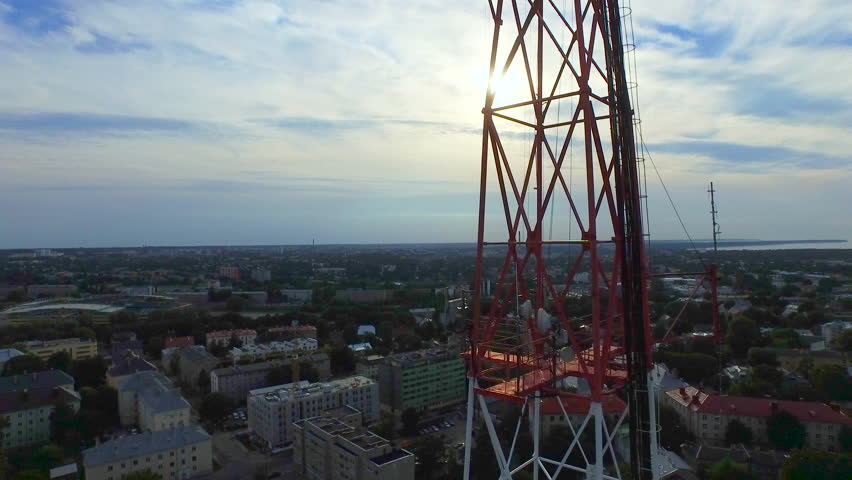 Aerial drone shot of a telecommunication radio tower mast in residential area. Shot in 4K (UHD).