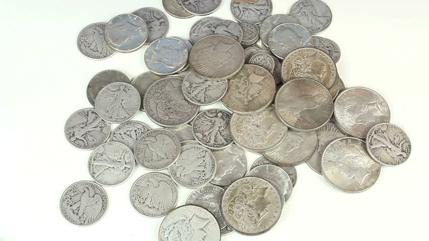 Hands sort through old, silver coins. 1080p