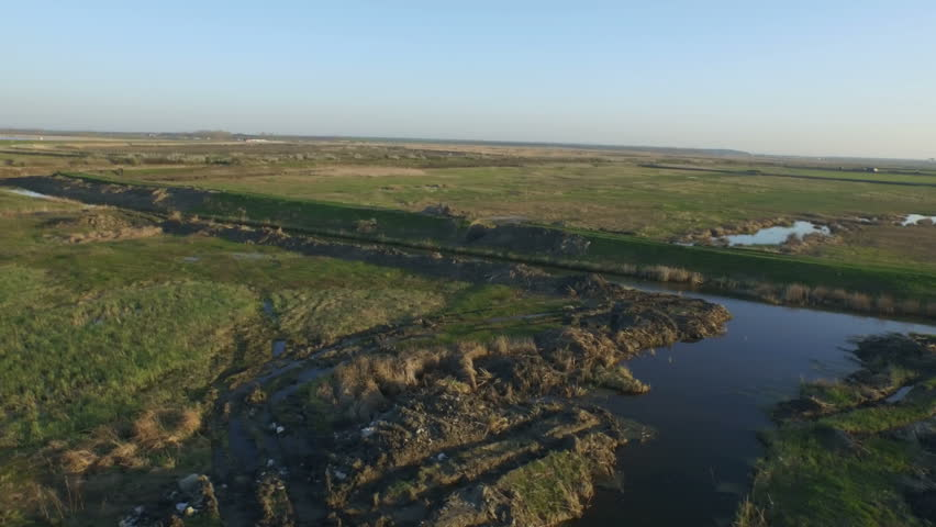 4K log drone shot of a green field and water   Shutterstock HD Video #11810630
