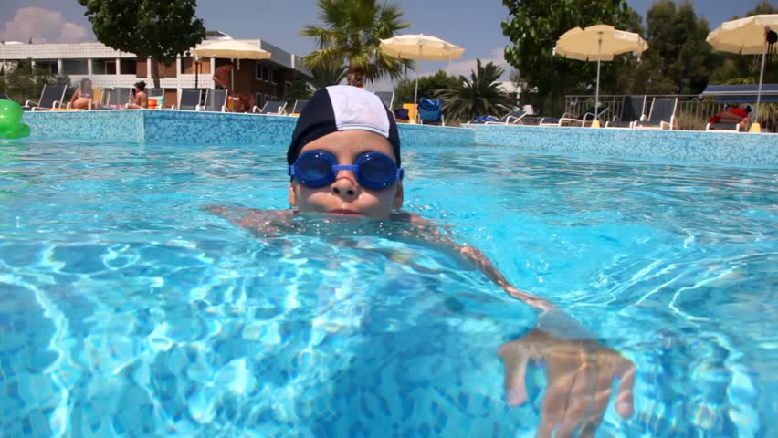 Boy in swimming goggles swimming in the pool water