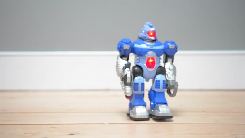 Toy robot walks then falls over onto its back. The robot is on a wooden floor with a grey colored wall behind it. The robot is blue in color and has red flashing lights