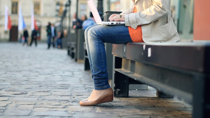 Woman with laptop sitting in urban environment, camera stabilizer shot