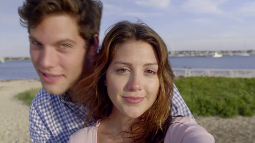 Closeup Of Cute Couple Taking Selfies Together On The Beach, Lighthouse In Background
