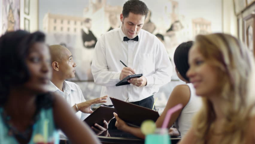 People, man and woman dating, boyfriend and girlfriend during date, young adult hispanic couple dining out in restaurant and talking to waiter in uniform. Dolly shot