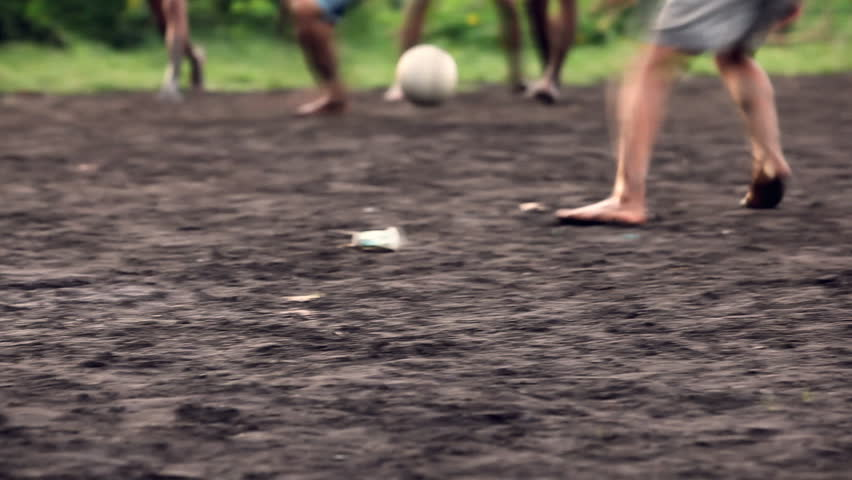 A gang of bar feet kids playing soccer on a muddy field. Serial of slow